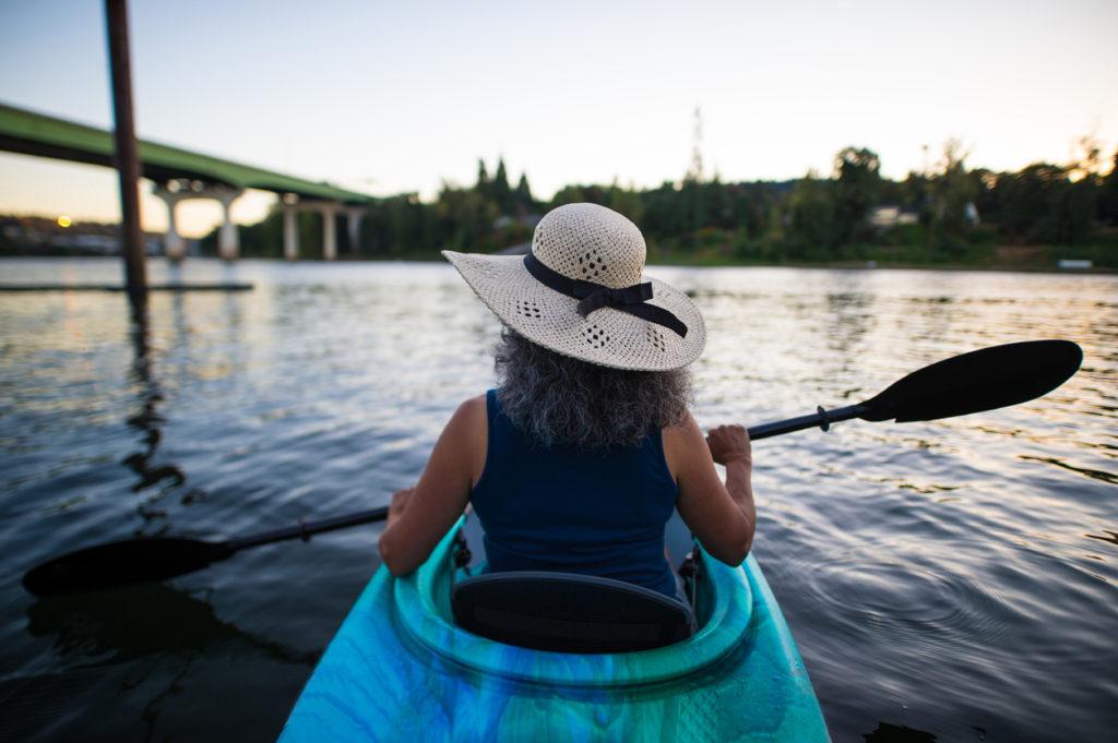 Ethnic female senior citizen kayaks in river