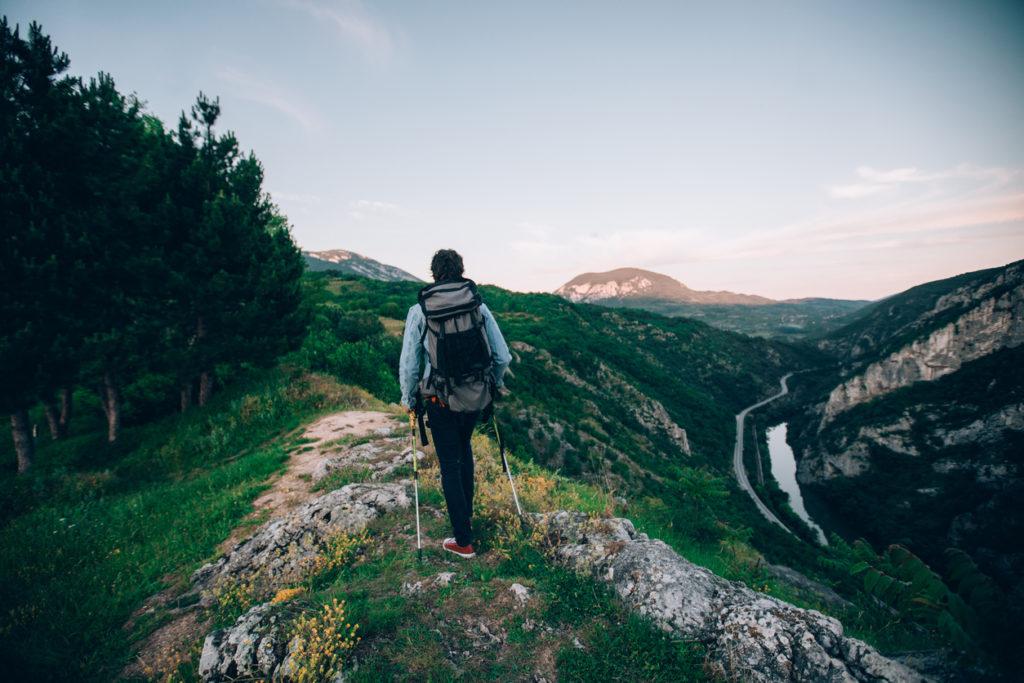 One man,walking high on mountain alone, enjoying the view, rear view.