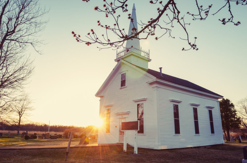 Small white church at sunrise in winter