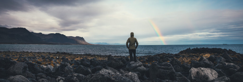 Woman watching rainbow over Icelandic landscape at Snaefellsnes peninsula (west parth of the island).