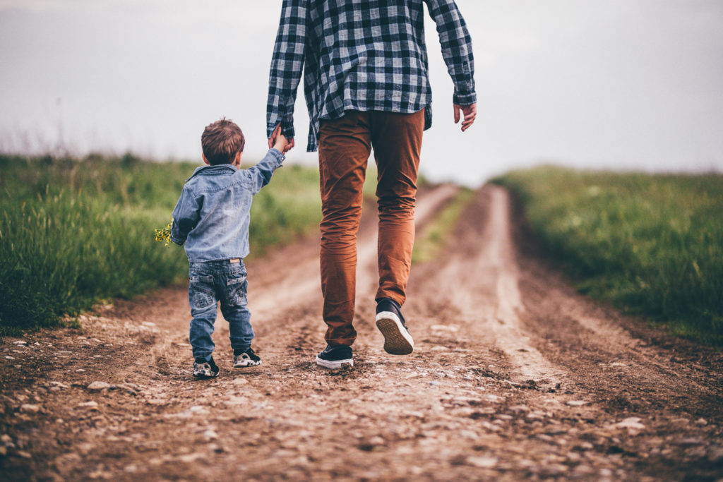 Father and son walking on an emoty country road and holding hands