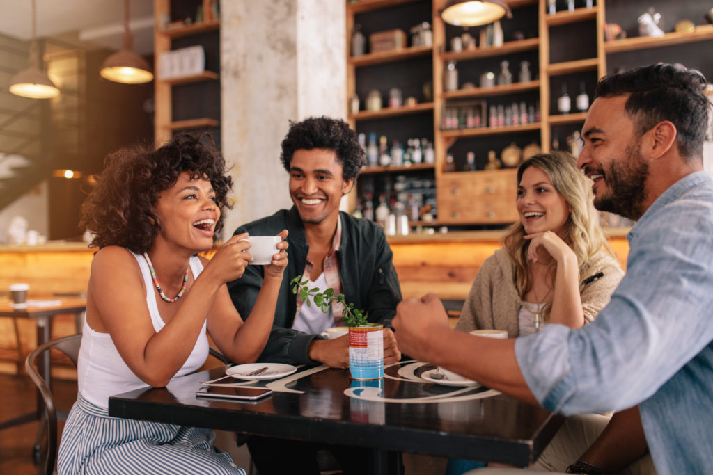 Young friends having a great time in restaurant. Multiracial group of young people sitting in a coffee shop and smiling.