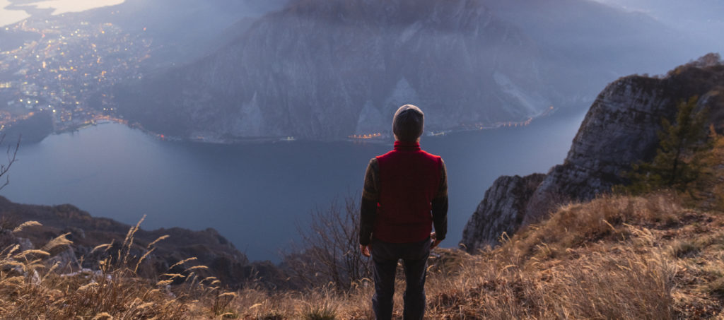 Hiker on the top of the mountain above the lake