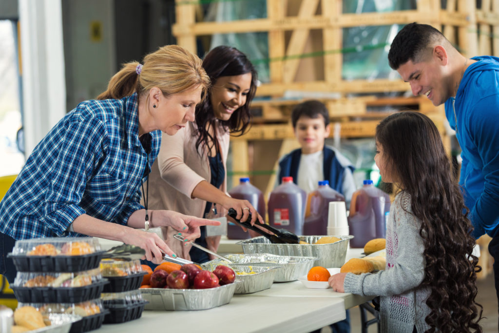 Two women serve family at soup kitchen.