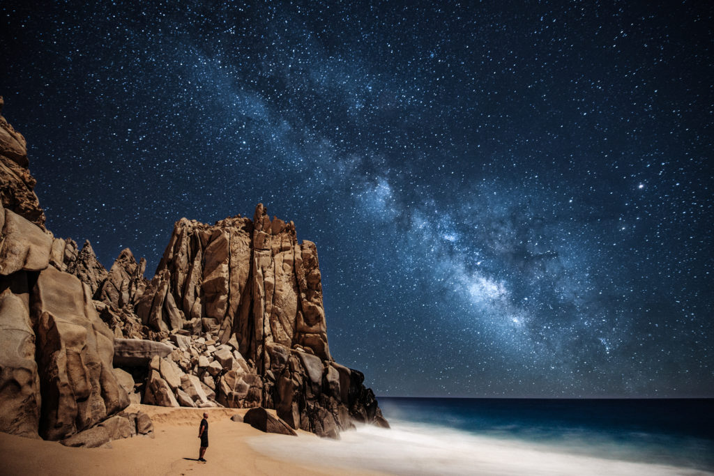 Lone person stargazing by the ocean in Cabo San Lucas