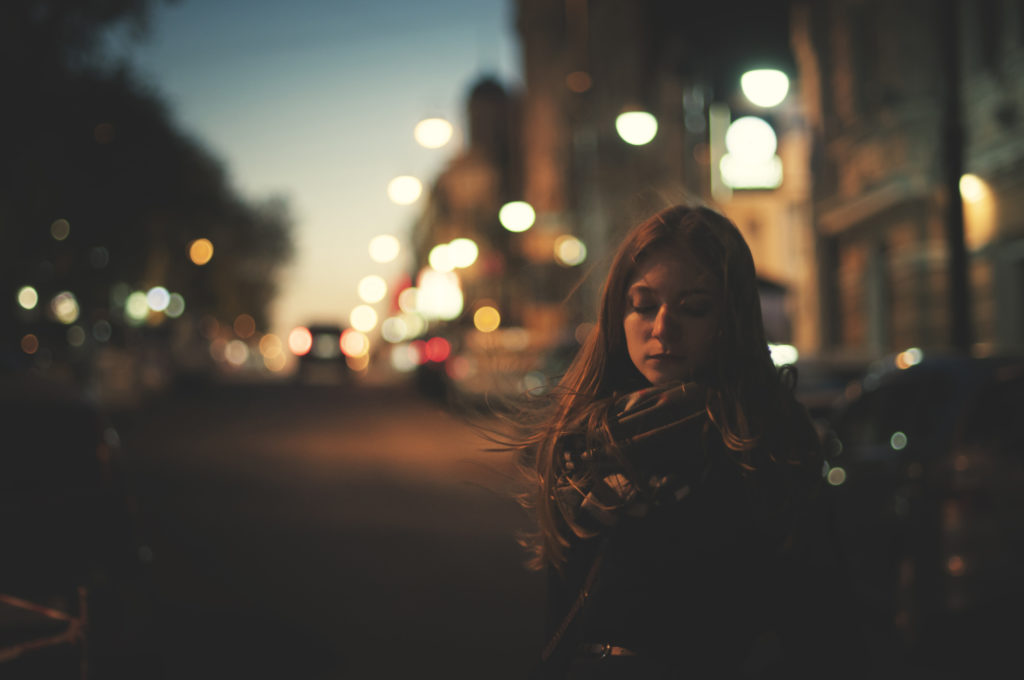 unhappy woman is walking alone on the night street