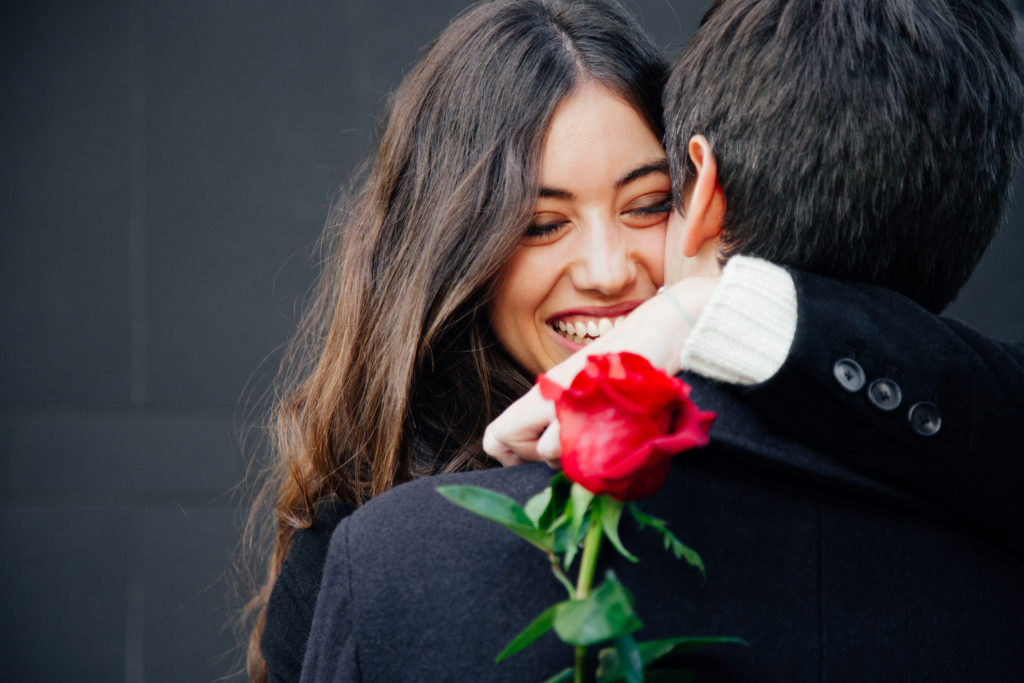 Beautiful and happy young woman in love hugging her husband holding a red rose