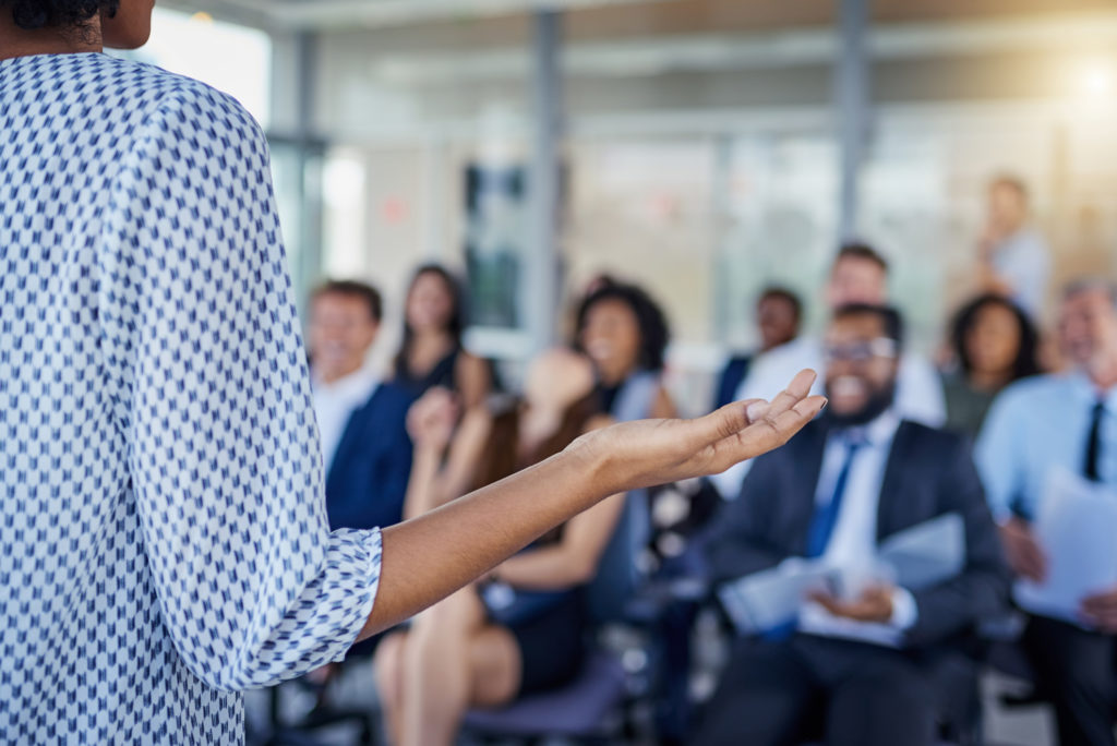 woman giving presentation in front of conference room full of business people