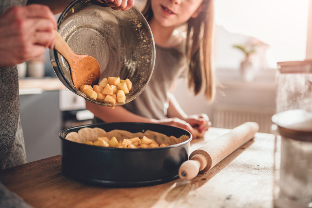 Woman pouring apple filling into baking pan her daughter standing beside her and helping