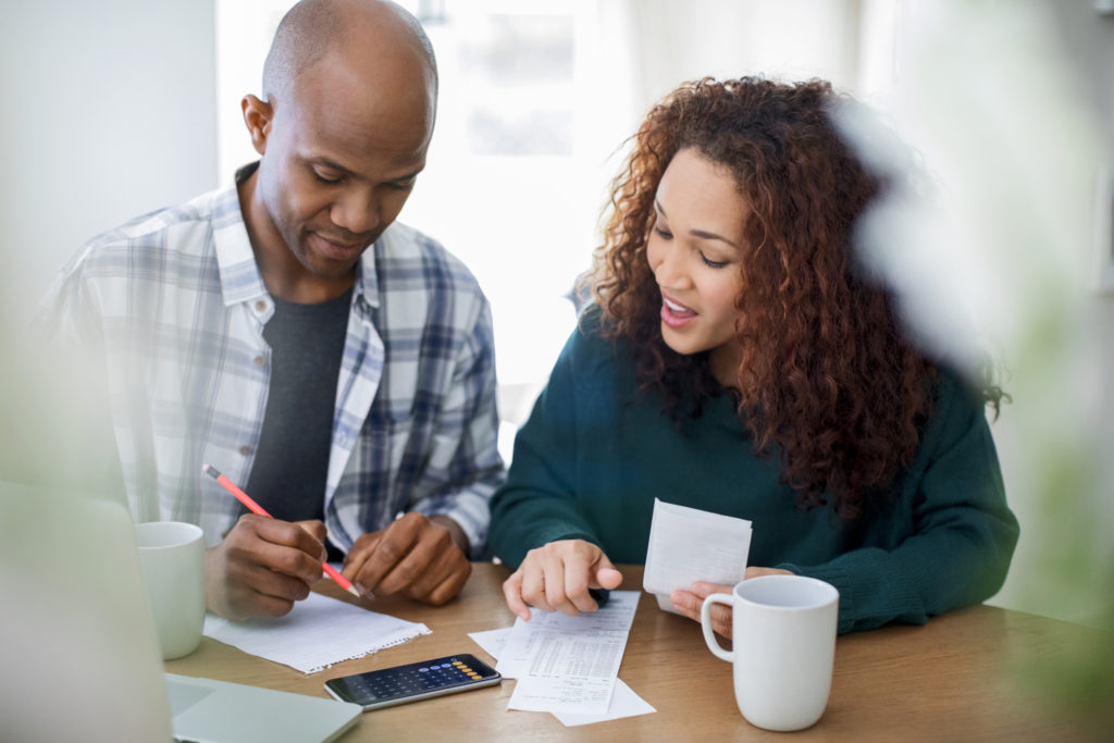 Couple calculating bills at table. Male and female are doing home finances. They are wearing casuals.