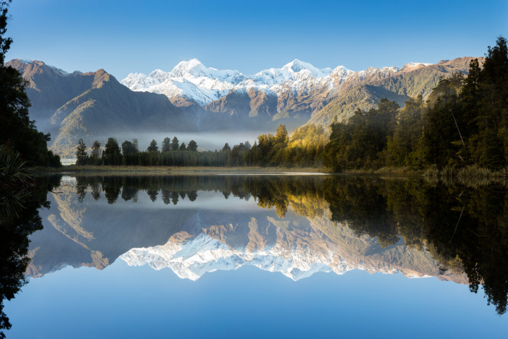 Reflections in the still waters of Lake Matheson on the South Island of New Zealand. Early morning mist remains as the rising sun illuminates the rain forest surrounding the lake. Lake Matheson is a popular destination for tourists visiting the West Coast of New Zealand. It is well known for its reflections of the surrounding forest and mountains, including New Zealand's tallest mountain Mount Cook.