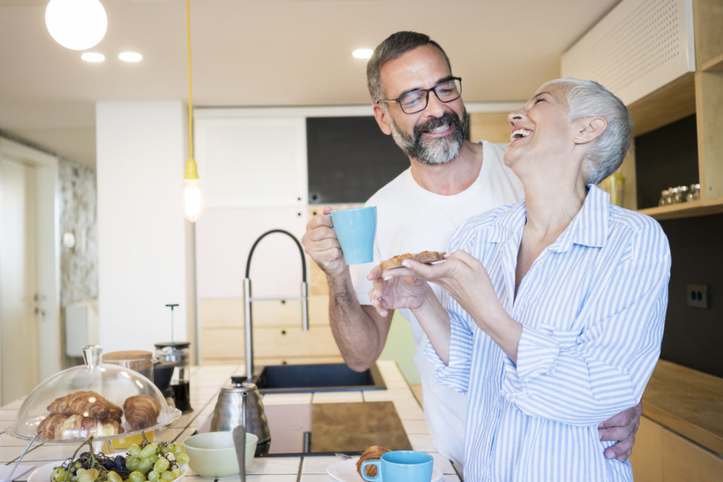 Beautiful couple in pajamas preparing breakfast in kitchen and drinking coffee