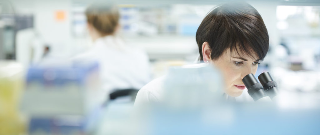 female scientist in a busy research lab