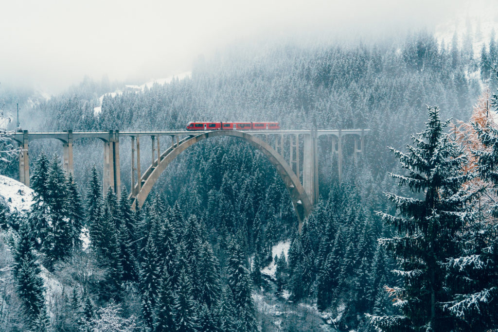 Scenic view of train on viaduct in Switzerland forest in winter