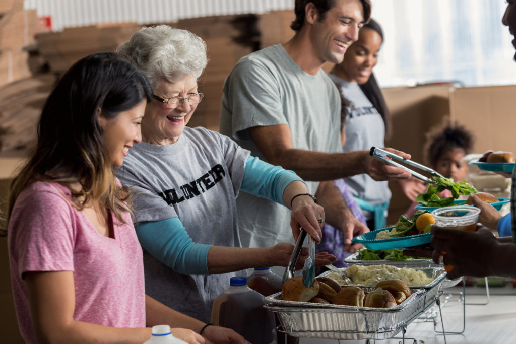 Cheerful senior woman and her friends or family serve meals to homeless people in a soup kitchen.