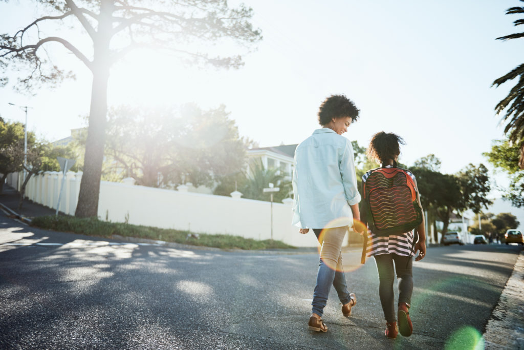 Rearview shot of a cheerful young mother and her daughter walking down the street together outside during the day