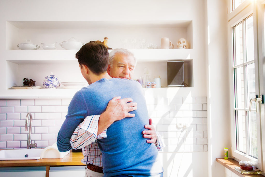 Senior man embraces mature son in sunny kitchen with a proud smile.