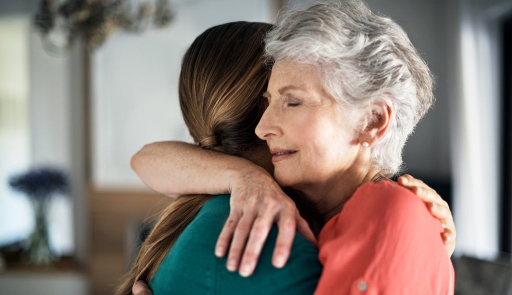 Shot of an elderly woman embracing her daughter at home