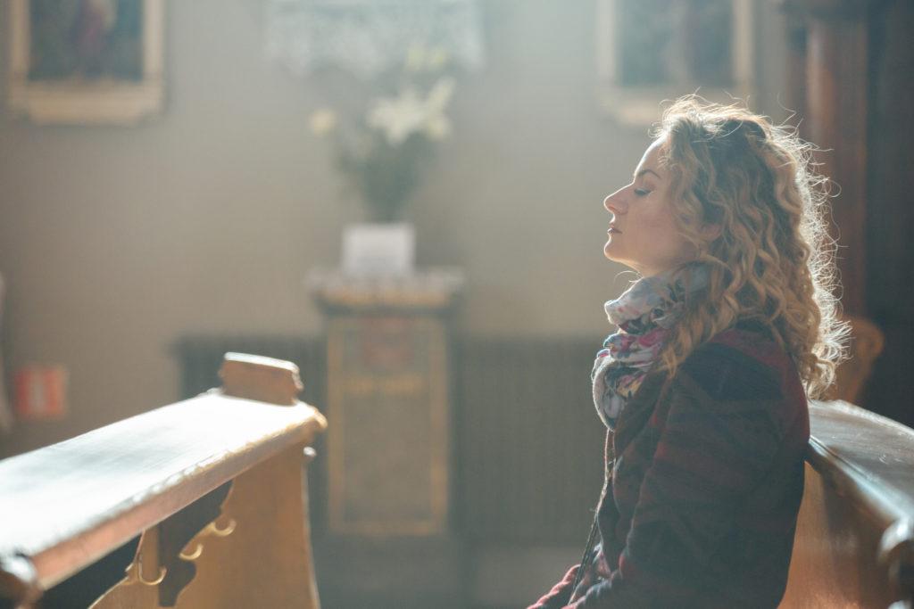 Young woman praying in the church.