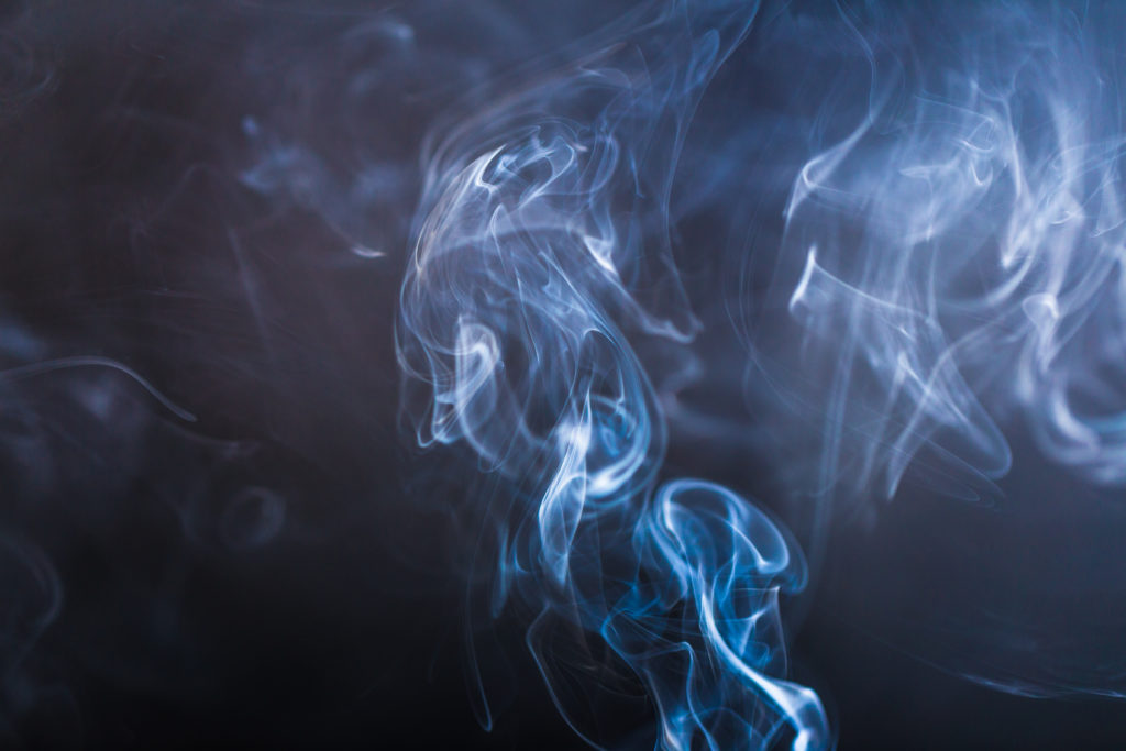 Blue swirling smoke abstract close up on black background