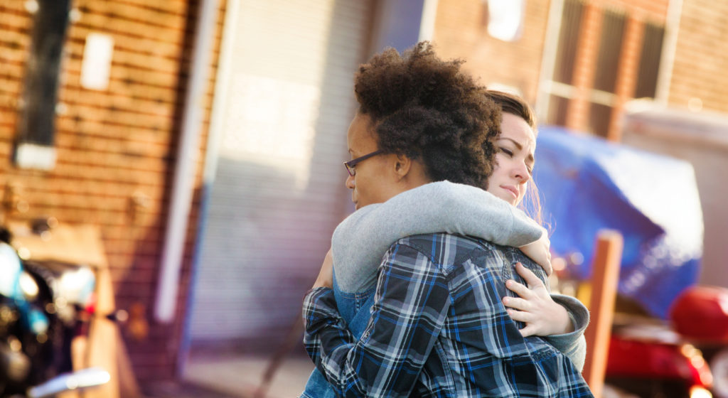 Young women forgiving each other with a hug in an alley. Tthey are both dressed in casual urban clothing. Photographed at sunset in Brooklyn. Letterbox format.