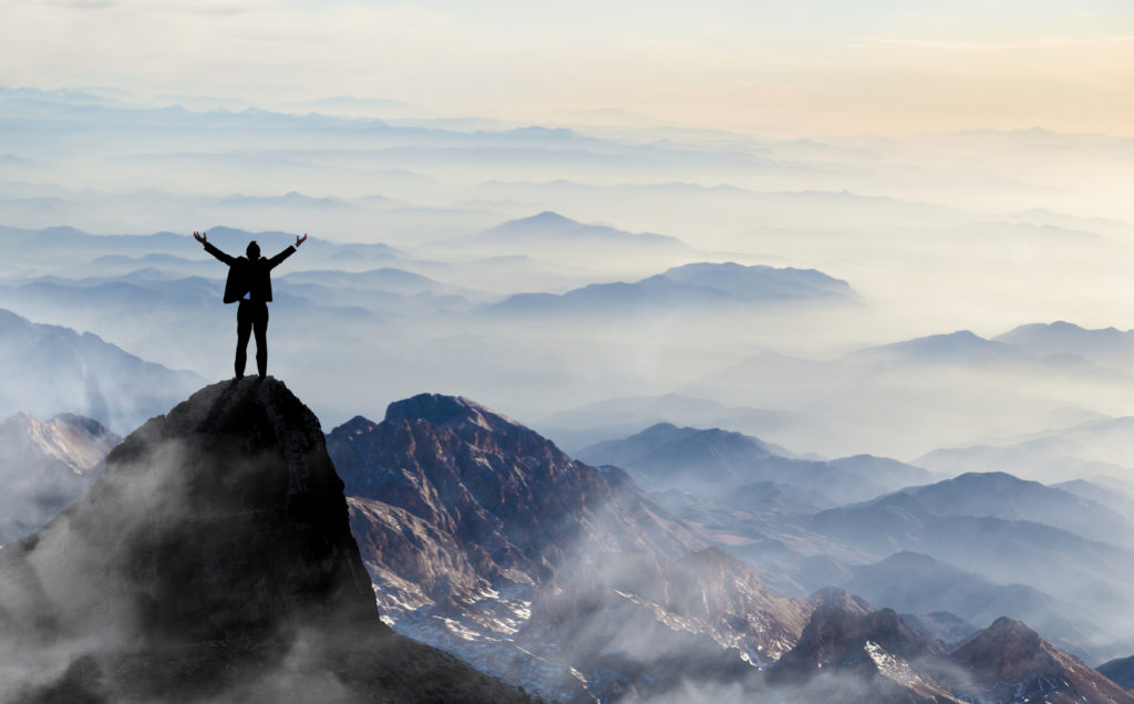 ambition leads man to mountaintop with arms raised
