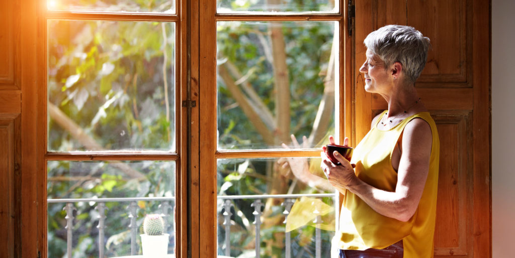 woman standing by a window at home drinking a cup of coffee