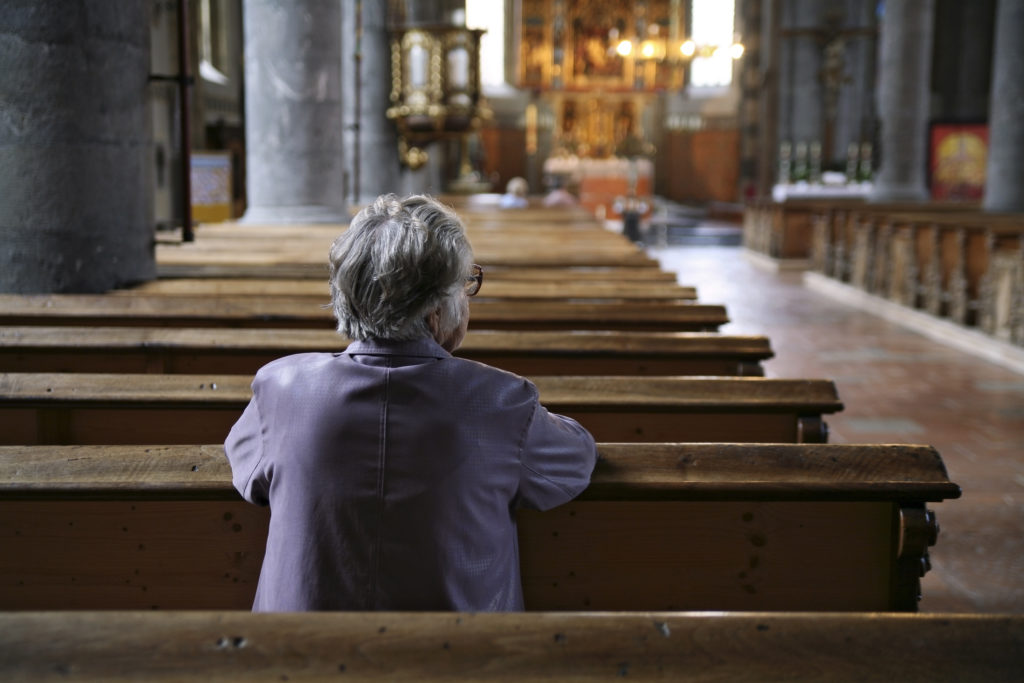 Older woman praying in an almost empty church. Shallow DOF, focus is on the woman