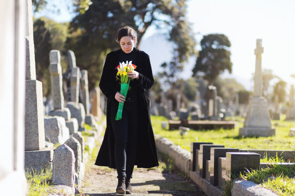 A young woman in black walks through cemetery headstones carrying flowers to the grave of someone she misses.
