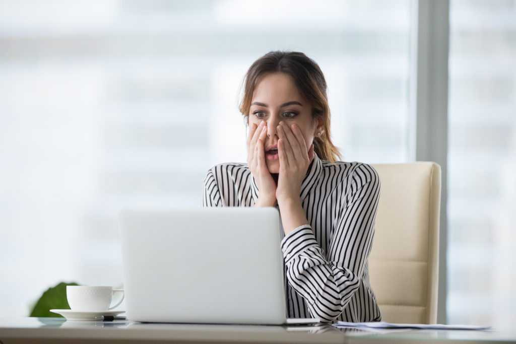 Shocked young woman looking at laptop screen. Frightened businesswoman receiving bad news, deal broke down, notification, bankruptcy, troubled with financial problems or debt.