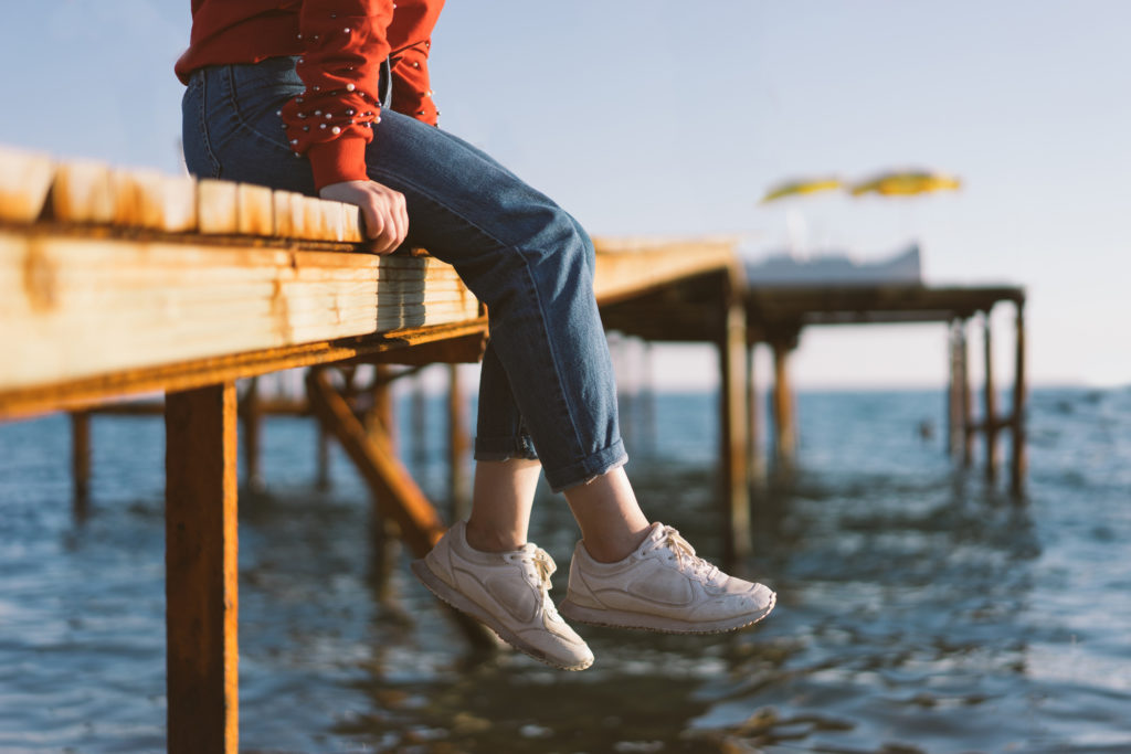 Woman's feet dangle from wooden wharf, above sea