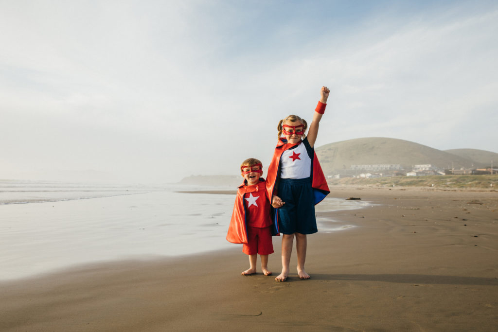 Young Girl and Boy Superheroes on California Beach.