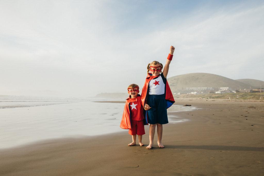Young Girl and Boy Superheroes on California Beach.