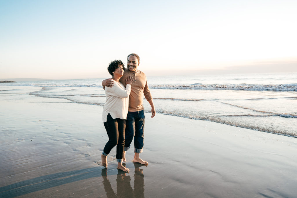 Senior men walking with senior women on the beach