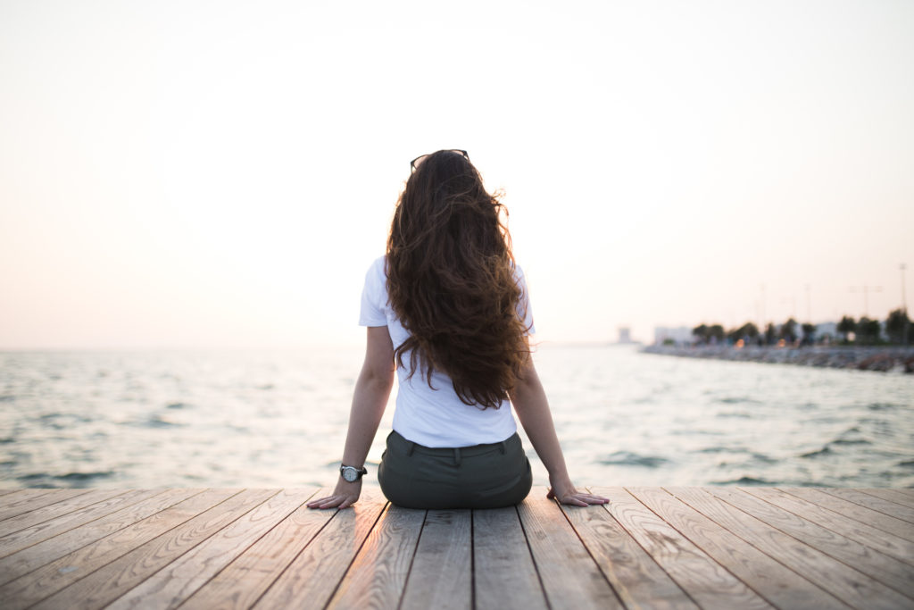 Young woman sitting looking sunset.