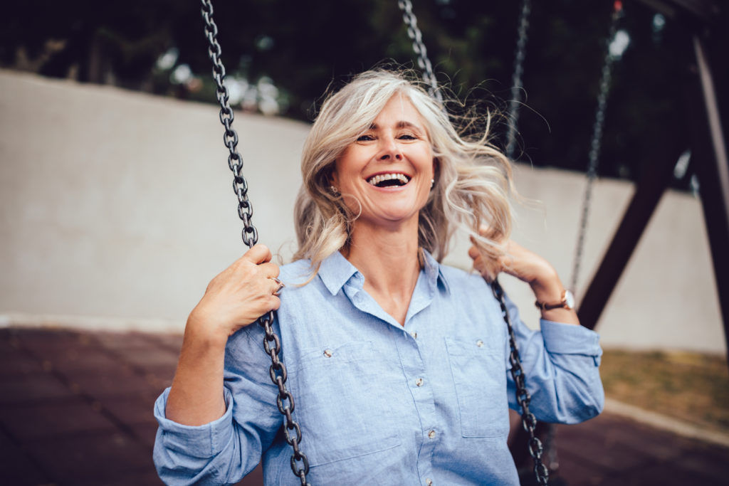 joyful senior woman with gray hair sitting on swing, having fun and enjoying retirement