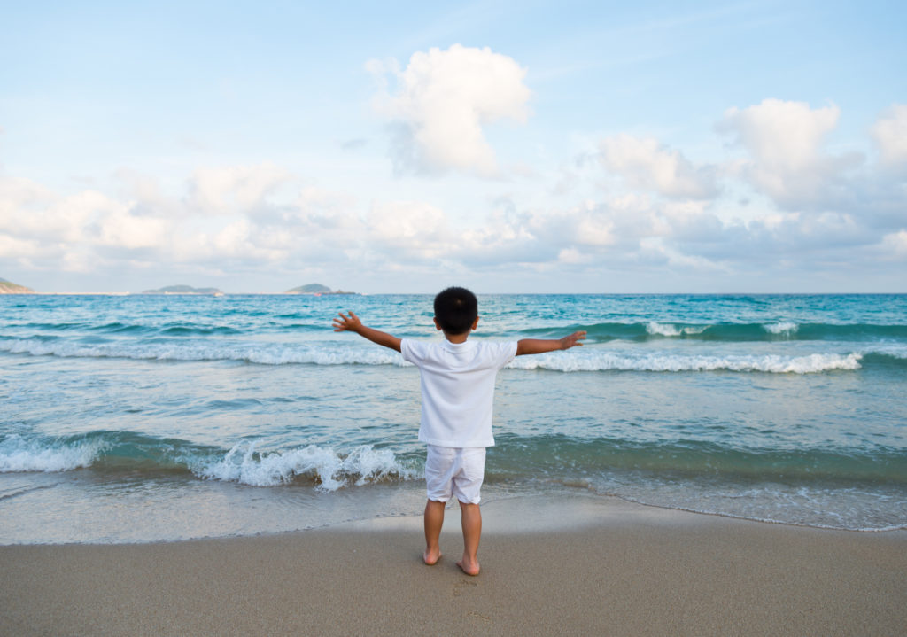 Little boy at the beach, arms outstretched
