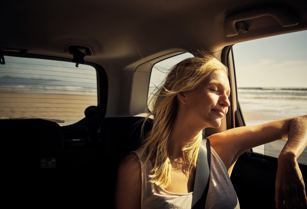 young woman enjoying breeze through open car window
