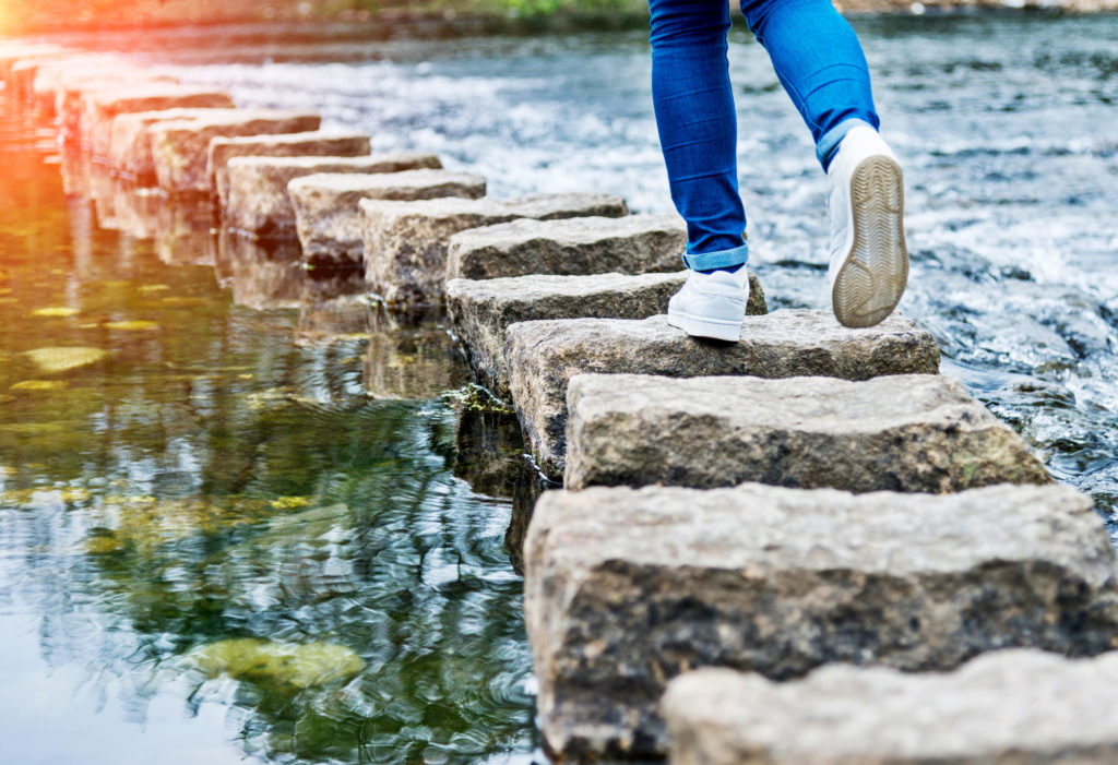 Woman paying close attention while crossing stepping stones on a river