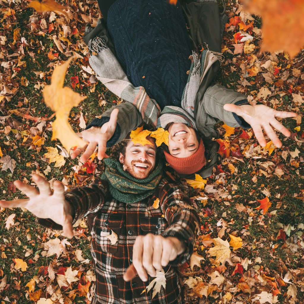 Couple playing in fall leaves