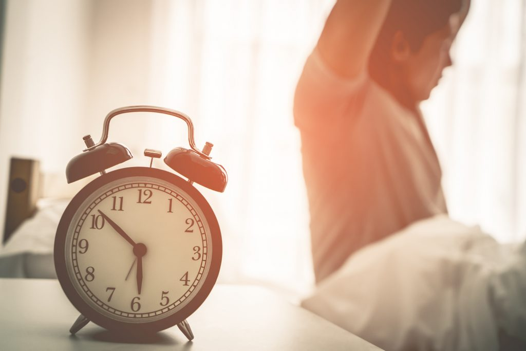 Man stretching behind alarm clock