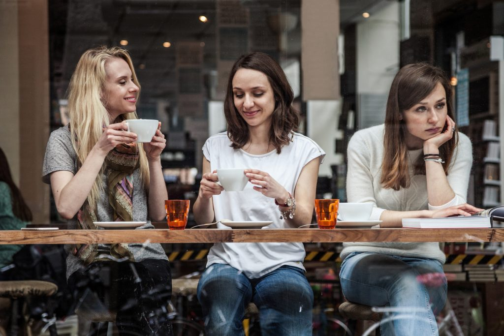 Group of women seated at a cafe's window. toxic friends
