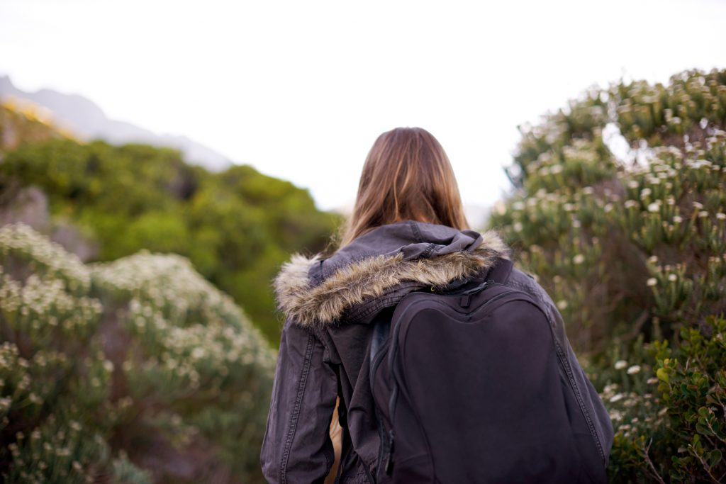 Rearview shot of a young woman hiking through nature