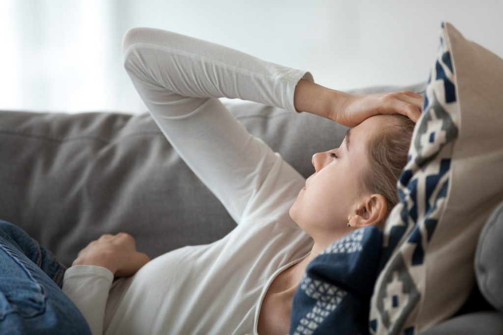 Upset depressed young woman lying on couch feeling strong headache