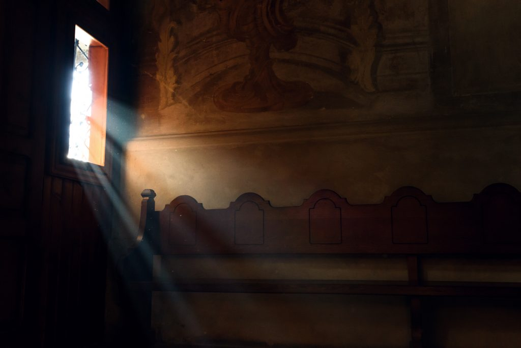 light falling through window in old church on wooden bench