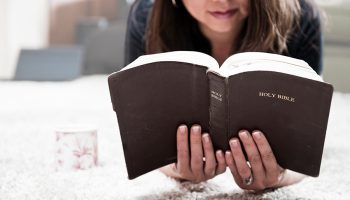 A female laying on a bed, reading her Bible