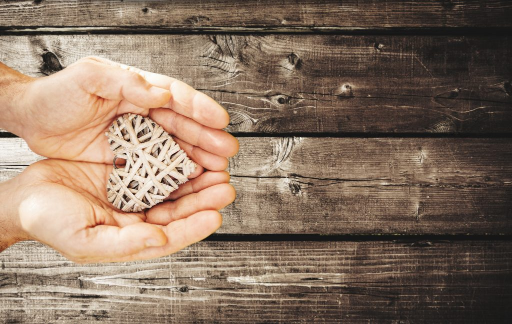 hands holding a woven wicker heart over wood background