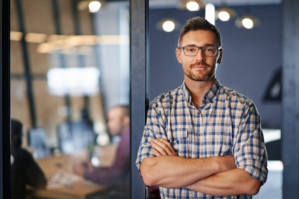 Portrait of a businessman standing with his arms crossed in the office