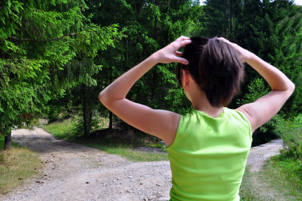 woman overthinking two options on trail