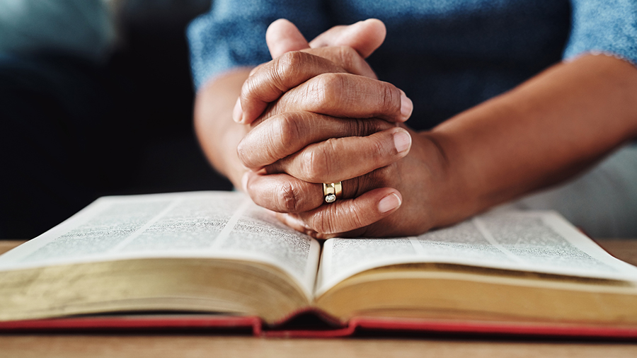 Folded female hands on a Bible